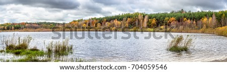 Panorama of autumn forest over lake, landscape with colorful trees and cloudy sky