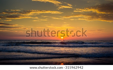 panorama of azure sea and fishing boat drifting against large bright sun disk rising from behind sea - stock photo