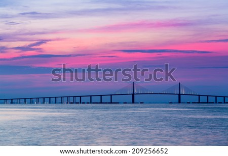 Panorama of bright sunrise lighting up the sky behind Sunshine Skyway Bridge from St Petersburg Florida across Tampa Bay. - stock photo