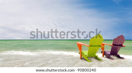 Panorama of colorful lounge chairs at a tropical beach in Miami Florida. Beautiful aqua green waters of the ocean and a blue sky  with clouds in the background - stock photo