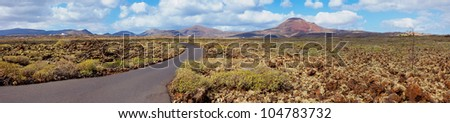 Panorama of empty road crossing the lava in the mountain, Lanzarote, Canary islands, Spain. Vertical view - stock photo