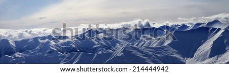 Panorama of evening mountains in clouds. Caucasus Mountains, Georgia. Ski resort Gudauri. - stock photo