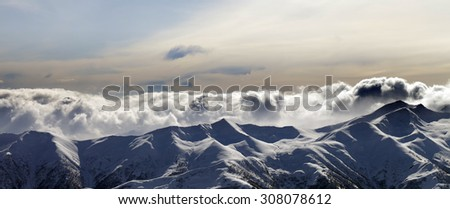 Panorama of evening mountains in clouds. Caucasus Mountains, Georgia, view from ski resort Gudauri. - stock photo