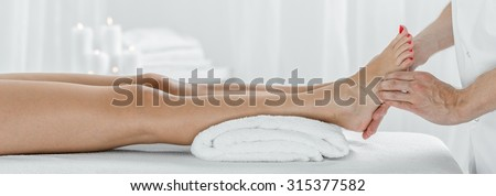 Panorama of female legs during acupressure therapy in massage studio - stock photo