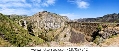 Panorama of four wheeler on cliff of canyon overlooking Boise river - stock photo