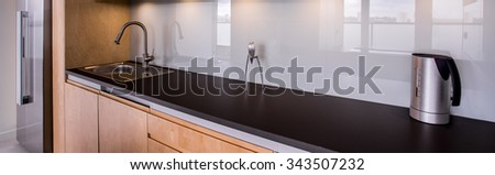 Panorama of functional kitchen interior with solid fixture - stock photo