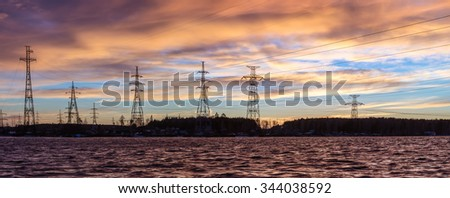 Panorama of high voltage power lines near water at sunset - stock photo