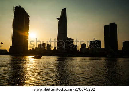Panorama of Ho Chi Minh viewed over Saigon river. Breathtaking dramatic light of sunset is highlighted by lens flare effect created by vintage photo equipment.