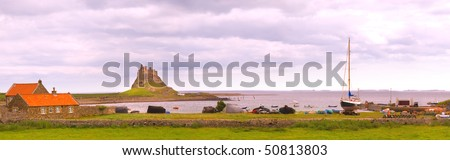 Panorama of Holy Island harbour and Lindisfarne Castle with tide in - stock photo
