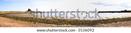 Panorama of Holy Island harbour and Lindisfarne Castle with tide out - stock photo
