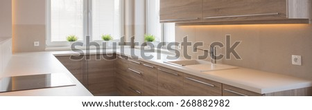 Panorama of kitchen interior with wooden cupboards - stock photo