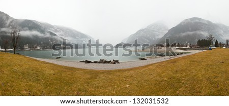 Panorama of lake with mountains in the clouds. Molveno lake. Italy. - stock photo