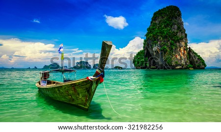 Panorama of long tail boat on tropical beach (Pranang beach) and rock, Krabi, Thailand - stock photo