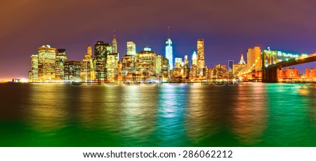 Panorama of Manhattan skyline and Brooklyn Bridge at night - stock photo