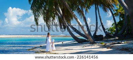 Panorama of mother and daughter on a deserted tropical beach - stock photo