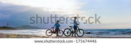 Panorama of mother and son biking on a beach at sunset - stock photo