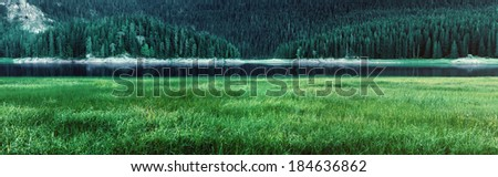 Panorama of mountain lake in the morning hours - stock photo
