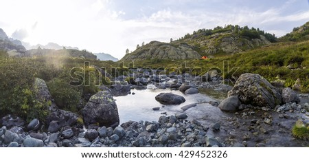 panorama of mountain scenery a sunny day with the tent on the meadow, located in the river valley in Abkhazia, the Caucasus Mountains - stock photo