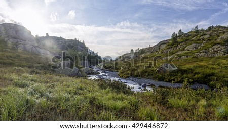 panorama of mountain scenery in sunny day with meadow, located in a river valley in Abkhazia, Caucasus Mountains - stock photo