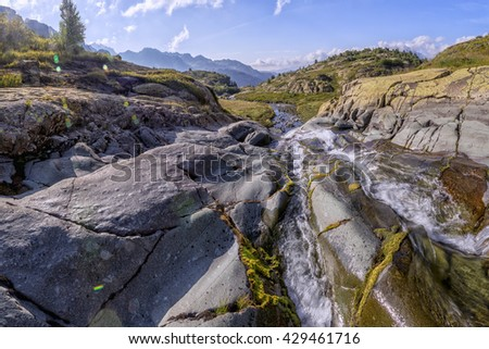 panorama of mountain scenery on a sunny day with a meadow situated in the valley of the river with a clean and transparent waters in Abkhazia, the Caucasus Mountains - stock photo