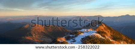 panorama of mountains covered with light snow. all lit yellow light of the sun. - stock photo