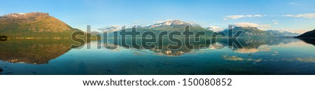 Panorama of norwegian fjord and mountains with clouds and reflection.