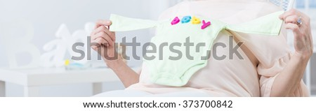 Panorama of older woman holding baby bodysuit expecting childbirth - stock photo
