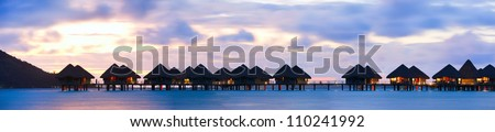 Panorama of over the water bungalows at sunset - stock photo