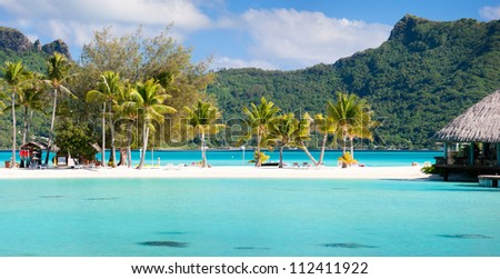 Panorama of perfect beach with coconut palms in French Polynesia - stock photo