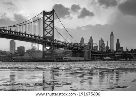 Panorama of Philadelphia skyline, Ben Franklin Bridge and Penn's Landing sunset in black and white - stock photo