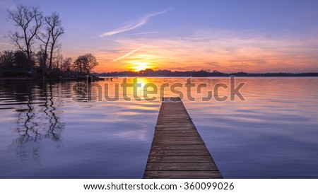 Panorama of  purple Sunset over Serene Water of Lake Paterwoldsemeer, Netherlands - stock photo