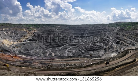 panorama of quarry extracting iron ore with heavy trucks,excavators,diggers and locomotives - stock photo