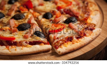 Panorama of sliced ham pizza with capsicum and olives on wooden board on table - stock photo