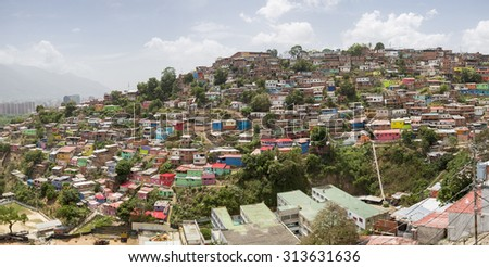 Panorama of small wooden colored houses in the poor neighborhood in Caracas. It cover the hills around Caracas and it is dangerous at all times. - stock photo