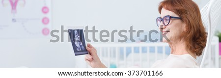 Panorama of smiling elderly pregnant female with ultrasound photo