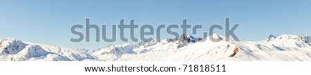 Panorama of snow mountain landscape with blue sky. Sunshine. Peaks. Rocks. Alps. France.