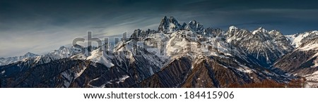 Panorama of Snow Mountain Range Landscape with dramatic sky  - stock photo