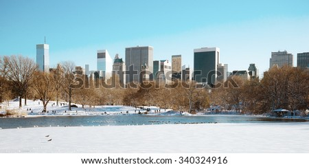 Panorama of snowy Central Park's Lake and Midtown Manhattan on clear winter day - stock photo