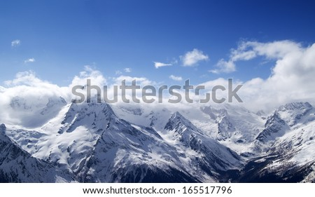 Panorama of snowy mountains in clouds. Caucasus, view from ski resort Dombay. - stock photo