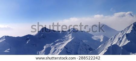 Panorama of snowy mountains in early morning fog. Caucasus Mountains, Georgia, ski resort Gudauri. - stock photo