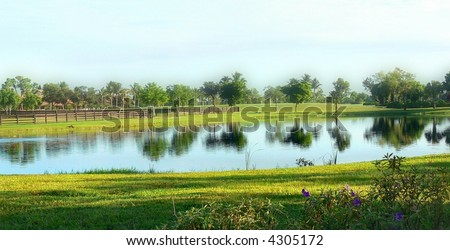Panorama of still pond with slight haze softening distant details in morning sun - stock photo