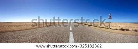 Panorama of straight road against a clear blue sky in the south of Morocco - stock photo