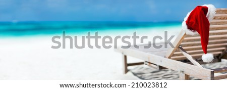 Panorama of sun lounger with Santa hat at beautiful tropical beach with white sand and turquoise water, perfect Christmas vacation - stock photo