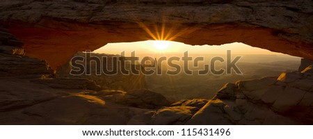 Panorama of sunburst through Mesa Arch in Utah's Canyonlands National Park - stock photo