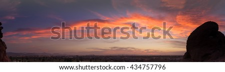 Panorama of sunset over late evening red sky over Phoenix,Arizona.  Papago Park buttes in foreground. - stock photo