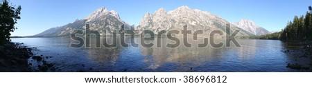 Panorama of Teton Range, reflecting in Jenny Lake - stock photo