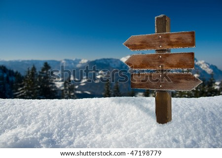 panorama of the alps with a wooden sign