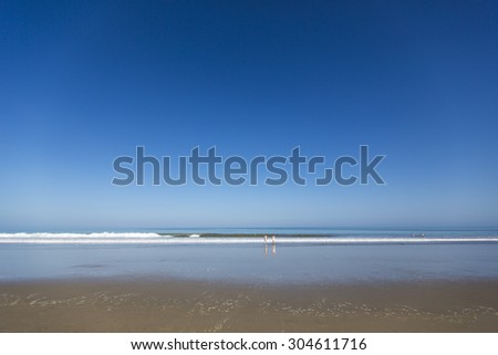 Panorama of the beach of Mancora with very few unrecognizable people swimming in the Pacific Ocean. Mancora, Peru 2015 - stock photo