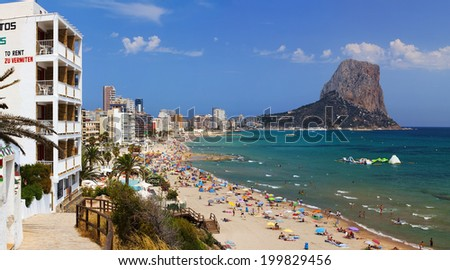 Panorama of the beach with people on a clear summer day (In the background the mountain Ifach, Calpe, Spain) - stock photo