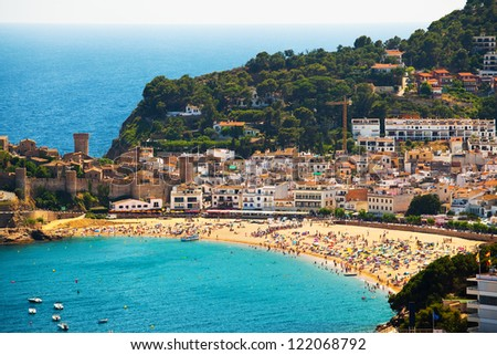 Panorama of the beach with swimming and sunbathing people (coast of Catalonia, Tossa de Mar City) - stock photo